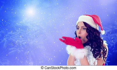 Girl in Christmas hat blowing flying snowflake on blue snow background. Group of flying snowflakes on clear blue winter sky.