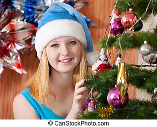 Girl in christmas hat near spruce