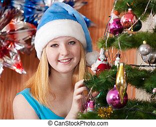 Girl in christmas hat near spruce