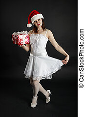 Girl in Christmas hat with gifts