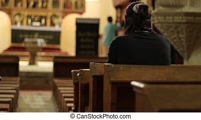 Girl in Church - Girl dressed in black shirt silently...