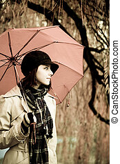 Girl in cloak and scarf with umbrella at park in rainy day. Photo in vintage style with nature colour.
