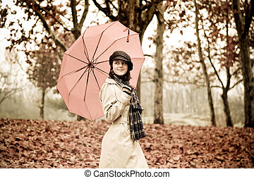 Girl in cloak and scarf with umbrella at park in rainy day....