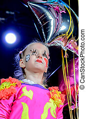Girl in Clown Costume Holding Star Shaped Balloon