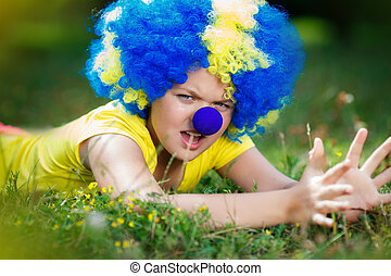girl in clown wig with blue nose is lying on the green grass in the park