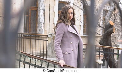 girl in coat posing behind the fence on the street 1
