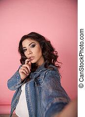 girl in denim jacket make photo on phone pink
