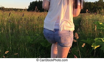 Girl in denim shorts goes through the long grass. Angle the...