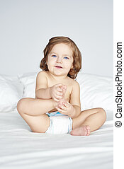 Girl in diaper sitting on bed