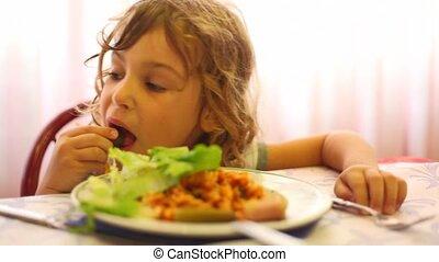 Girl in dining room hands eats leaf of lettuce, pizza