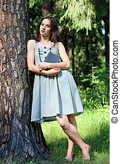 girl in dress near tree with book