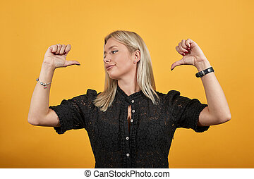girl in dress on yellow background stylish cool woman points fingers at herself