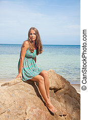 girl in dress sitting on a rock by the sea
