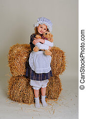 Girl in dress standing near a rustic vintage hay with a toy.