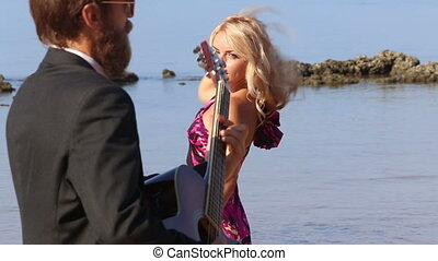 girl in dress with bow  flirts dancing by  guitarist on beach