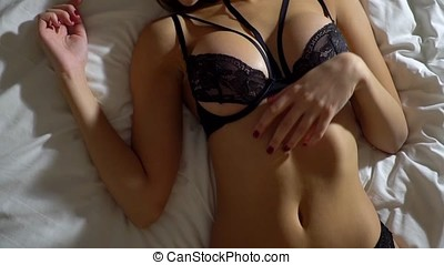 Girl in erotic black underwear lies on a bed and poses sexually in front of the camera. Slow motion. Close-up.