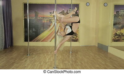 Girl in excellent physical shape performs trick on pole -...