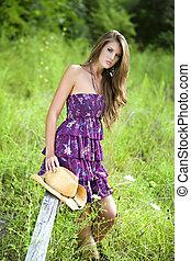 Girl in field sitting on a rail