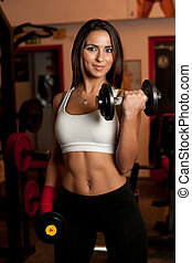 Girl in fitness club - Beautiful young woman working out in ...