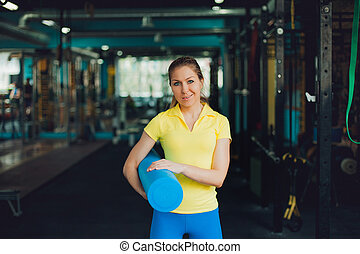 Girl in fitness club. Young female athlete with a Mat for stretching in the hands, ready to workout