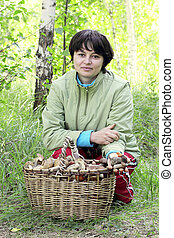 girl in forest next to a basket of mushrooms