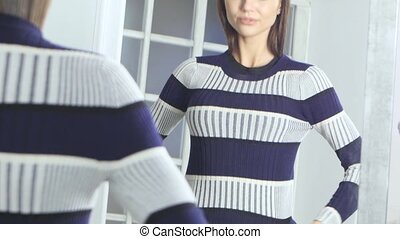 Girl in front of a mirror dresses a sweater. Close up - Girl...