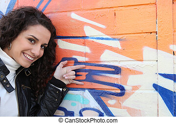 Girl in front of graffiti wall
