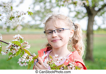 girl in glasses and blossoming twig of tree
