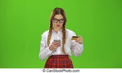 Girl in glasses dials numbers on the phone with a gold card. Green Screen