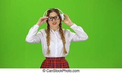 Girl in glasses listens to music on headphones . Green...