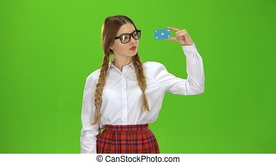 Girl in glasses raises a card and shows a thumbs up smiling...