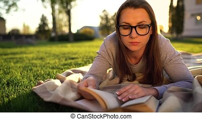 Girl in glasses reading book lying down on a blanket in the...