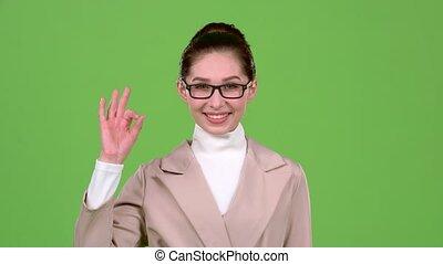 Girl in glasses shows ok. Green screen. Slow motion - Girl...