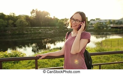 Girl in glasses talking on the phone on a city bridge on the sunset.