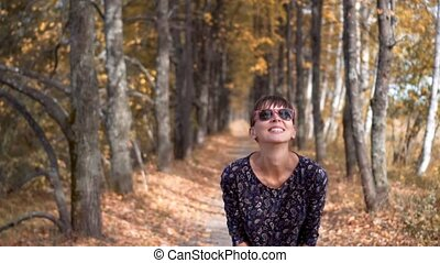 girl in glasses throwing leaves in the forest. slow motion