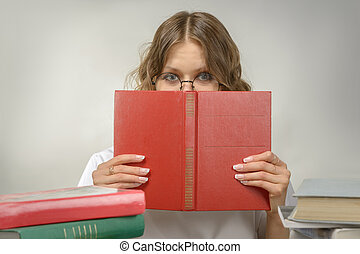 Girl in glasses with a red book