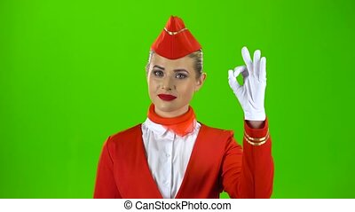 Girl in gloves shows a okey. Green screen