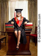 girl in graduation cap sitting on desk between piles of books