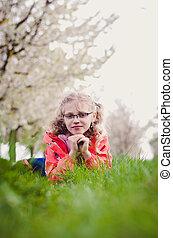 girl in grass in springtime lying in the grass