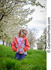 girl in grass in springtime sitting in the grass