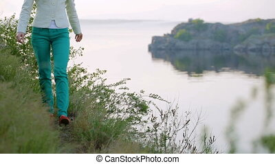 Girl in green pants walks along path along river to the...