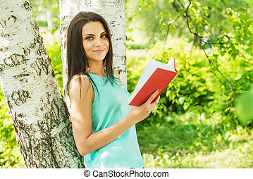 Girl in green park read book in summer sun ligh