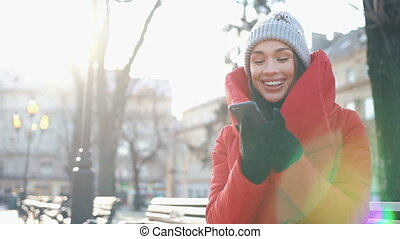 Girl in grey hat and red coat talks on skype video chat while she sits on the bench on the street in a sunny winter day