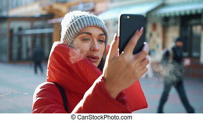 Girl in grey hat and red coat talks on skype video chat while she stands on the street in a sunny winter day