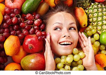 Girl in group of fruit.