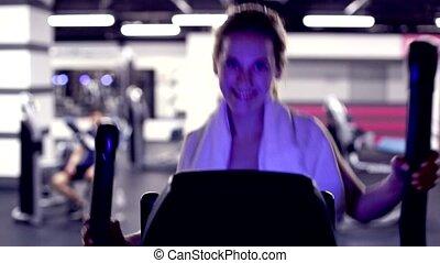 Girl in gym on elliptical trainer