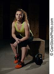 Girl in gym sitting on a pedestal