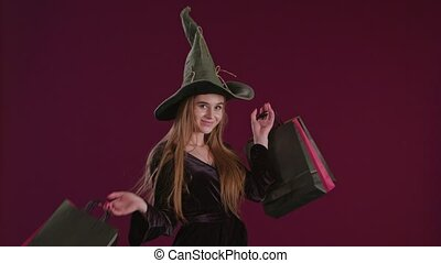Girl in Halloween Witch Costume with Shopping Bags. - Girl...