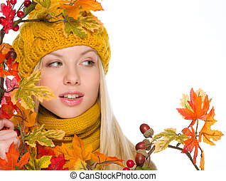 Girl in hat and scarf with autumn bouquet looking on copy space