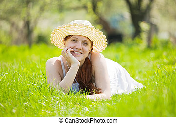 girl in hat lying on  grass